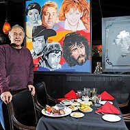 Jamil's owner Greg Gawey stands next to one of the restaurant's murals featuring famous Oklahomans.