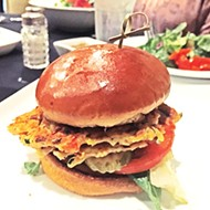 The veggie burger features two patties with a  hummus base and sauteed vegetables.