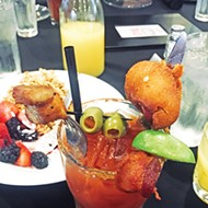 A bloody mary topped with a housemade corn dog, bacon and pork belly
