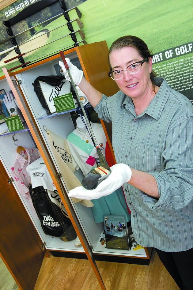 Curator of the collections Deborah Baker holds a golf club used by Danny Edwards at the Edmond Musuem.Photo/Shannon Cornman - SHANNON CORNMAN
