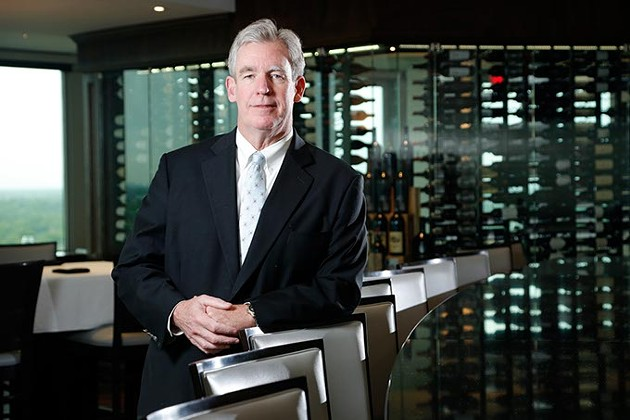 Kevin George pauses in front of the custom-built wall display of wines in The George Prime Steakhouse, his restaurant located atop Founders Tower. (Garett Fisbeck)