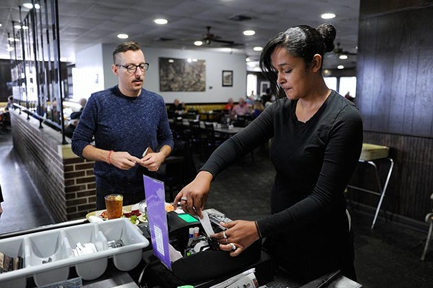 Stacey Jones works the cash register as Lennon Patton buys his food at Boulevard Cafeteria in Oklahoma City, Friday, Dec. 11, 2015. - GARETT FISBECK