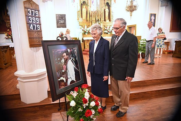 Sister Marita Rother and Tom Rother, siblings of Father Staley Rother with their deceased brothers portrait, after the Anniversary Mass for Father Stanley Rother at the Holy Trinity Catholic Churche in Okarche Oklahoma on Aug. 1.  mh