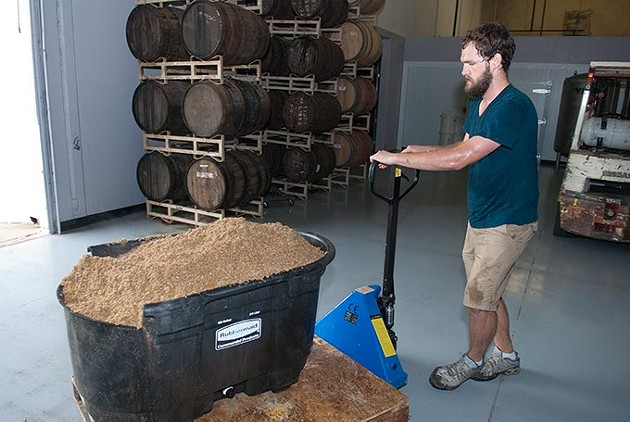 Partner Will Perry transports used mash past the bourbon and whiskey barrels (Mark Hancock)