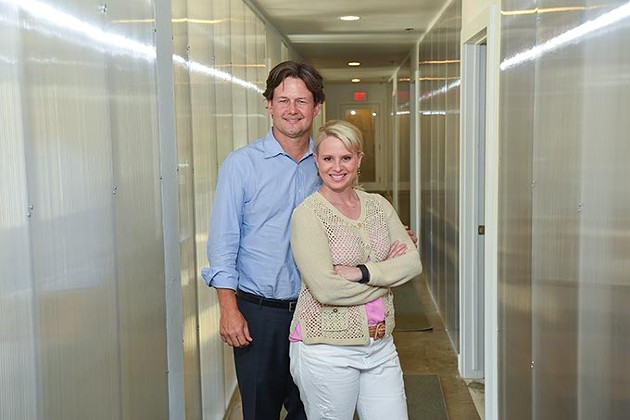 Heather & Keith Paul in a glass hallway at A Good Egg. mh