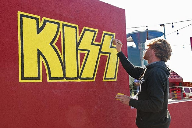 Local artist Rick Sinnett puts finishing touches to some yellow fill in the KISS logo, one of many rock & roll iconic band photos and logos decorating the outside of Rock & Brews restaurant, 2737 W. Memorial Road, 10-27-15. - MARK HANCOCK