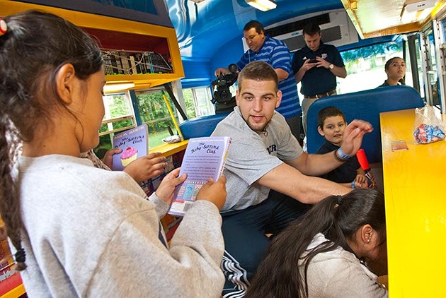 Rookie Thunder forward, Mitch McGary, helps Putnam Heights Elementary students pick out books inside the Rolling Thunder Book Bus, 9-11-2014.  mh