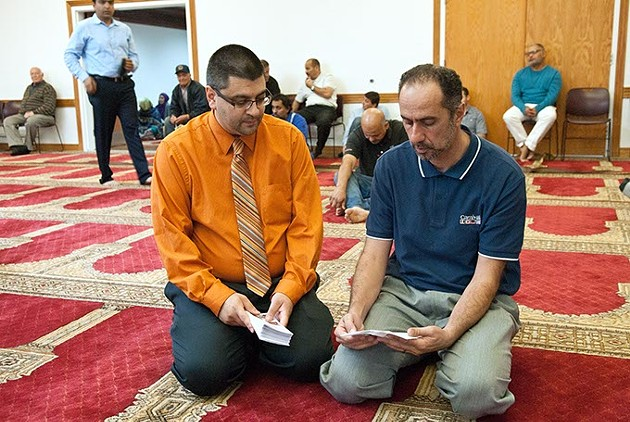 Adam Soltani, CAIR executive director, discusses a pamphlet with a member of the Islamic Society of Oklahoma apon his arrival for the 2:00 prayer service.  mh