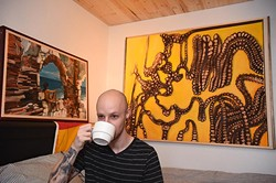 """Moore artist, Maurice Perez, sips on coffee in front of his works, (left to right) """"Calling"""" and """"Rule of Three"""", 9-24-15. - MARK HANCOCK"""