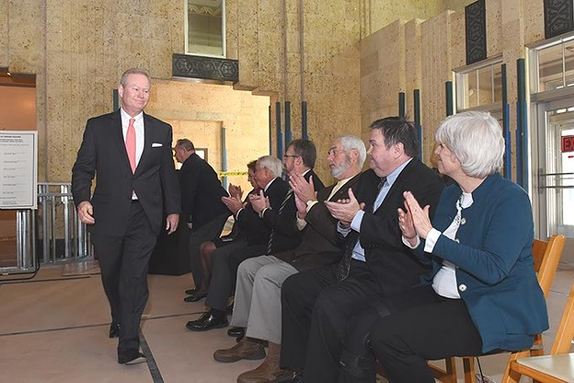 Oklahoma City Mayor Mick Cornett walks to his seat after speaking while five other mayors of the metro area and other officials applaud, during a signing ceremony held in the historic Santa Fe Station, being designated the regioal transit hub, in downtown OKC, 12-1-2015. - MARK HANCOCK