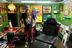 Rawb Carter poses for a photo at his booth at Mind Bender Tattoo Shop in Oklahoma City, Wednesday, July 22, 2015. - GARETT FISBECK