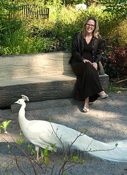 Louisa McCune-Elmore, executive director for the Kirkpatrick Foundation, poses with a peacock in the Children's Petting Zoo at the Oklahoma City Zoo in this 1012 file photo.  mh