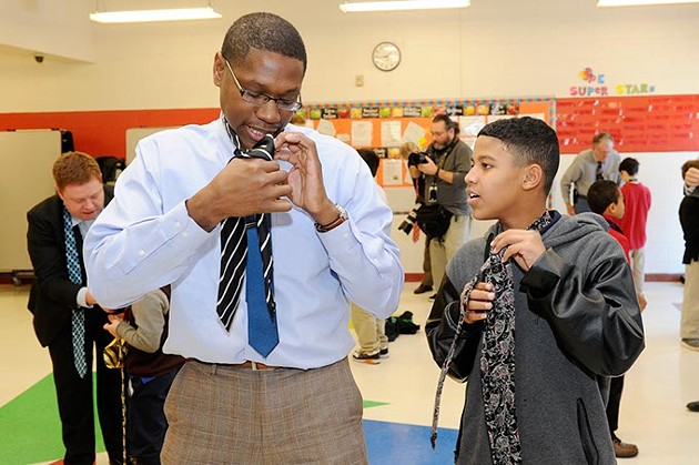 Harold Rayfield shows Trayvon Lowery how to tie a tie during Tie Day at Edgemere Elementary in Oklahoma City, Thursday, Jan. 14, 2016. - GARETT FISBECK