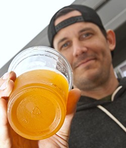 Josh Sylvester, bartender and everything else at The Bleu Garten, displays a recycle symbol on the bottem of one of its draft beer cups. (Mark Hancock)