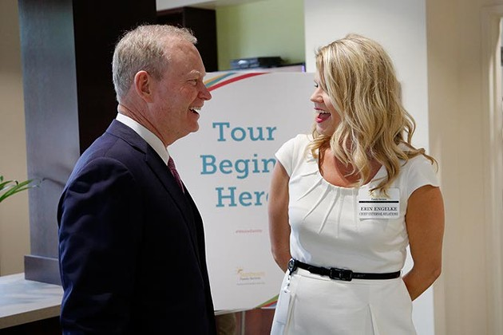 Mayor Mick Cornett talks with Erin Engelke during a grand opening ceremony at Sunbeam Family Services in Oklahoma City, Thursday, May 7, 2015. - GARETT FISBECK