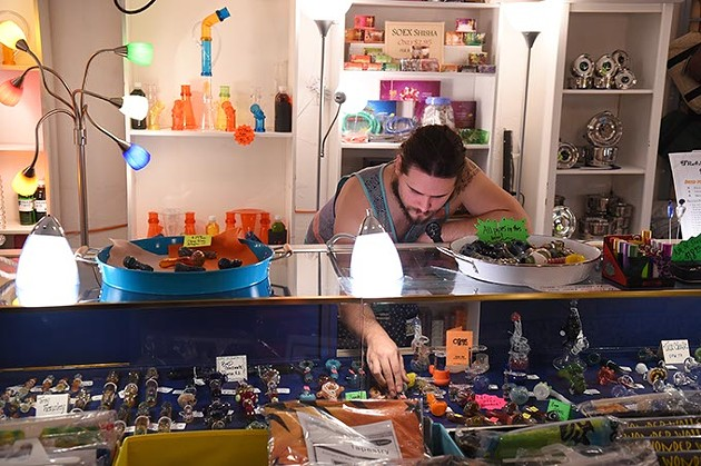 Brandon Martin, store manager, arranges glass pipes, at The Indigo Attic in Oklahoma City, 11-11-15. - MARK HANCOCK