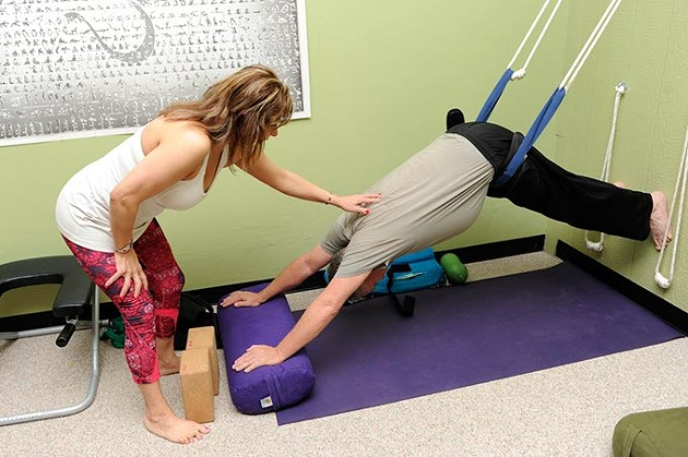 Sara Alavi helps Veteran Jack McCallister with a pose during a Yoga class at Yoga Home School of Therapeutics in Oklahoma City, Friday, March 20, 2015. - GARETT FISBECK