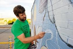 Scott Henderson works on a mural outside Antique Avenue in Oklahoma City, Monday, Oct. 26, 2015. - GARETT FISBECK