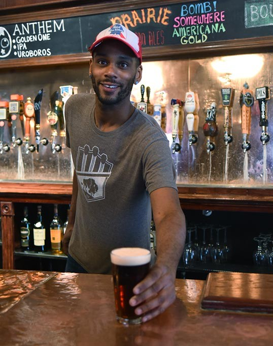 Day bartender Wallace McLeod serves a Newcastle Brown Ale at TapWerks.  mh