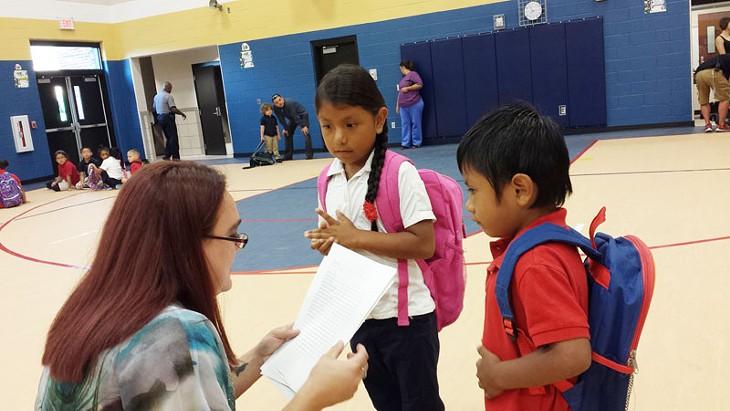 A Mark Twain Elementary teacher helps new students find their class. - BEN FELDER