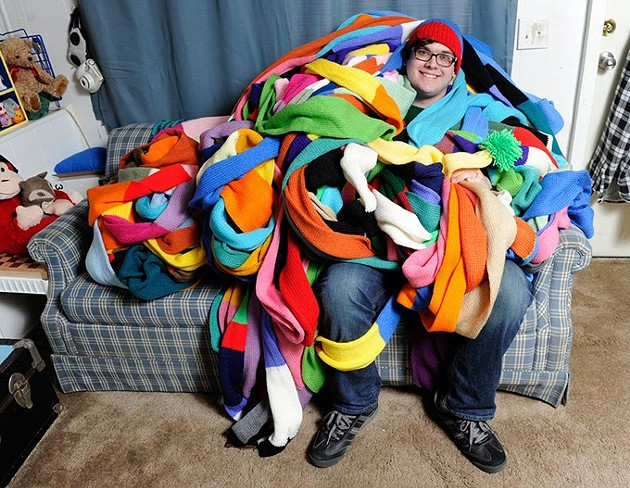 Aaron Miller poses for a photo with his 800-foot knit hat at his home in Oklahoma City, Friday, Jan. 29, 2016. - GARETT FISBECK