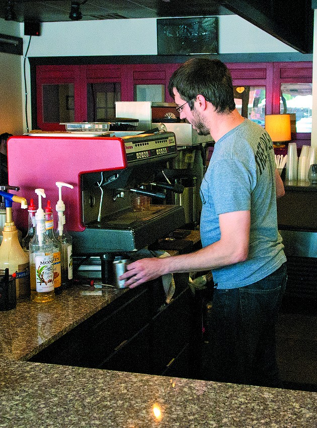 Jason Weigand works behind the counter at District Coffee House. (Mark Hancock)