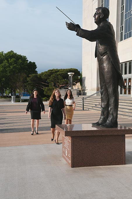 From left, Jenni Fosbenner, Allison Goodman, and Cheryl Brashear, board members with the Overture OKC Philharmonic support group, walk under the conductor sculpture in front of the Civic Center Music Hall in Downtown OKC recently.  mh