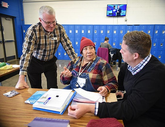 Tom Jones, left, and his son Adam Jones of the City Rescue Mission, chat with Marilyn Bond, a Choctaw Native American homeless woman, preparing with help from City Rescue Misson, to attend the Mayor's Breakfast, by invitation from Norman Mayor Cindy Rosenthal, to be held in Norman on January 18th, 1-7-16, in the Women's section of City Rescue Mission in Downtown OKC. - MARK HANCOCK