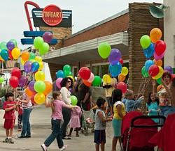 Balloons outside Photo Art Studio add even more local color to Plaza Fest, celebrating it's 16th birthday Saturday.