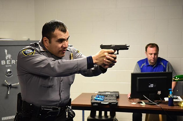 Captain Paco Balderrama fires of a few rounds during a police training simulation using CO2 cartriges and electronics, with Sargent Shawn Byrne controlling the scenario from a computer in background.  mh