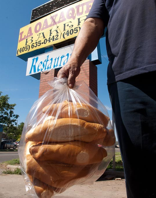 A customer carries out a clear bag full of fresh bread from La Oaxaquena Bakery, 741 SW 29th Street. (Mark Hancock)