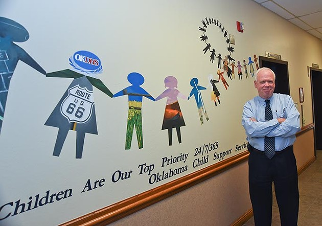 Oklahoma Child Support Services Director, Gary Dart, near the entrance of their offices with fun, hallway art.  mh