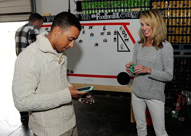 Sean Johnson donates to the Food For All truck as Adrian Young looks on during COOP Ale Works Tap Room Halloween Party, Saturday, Oct. 24, 2015. - GARETT FISBECK