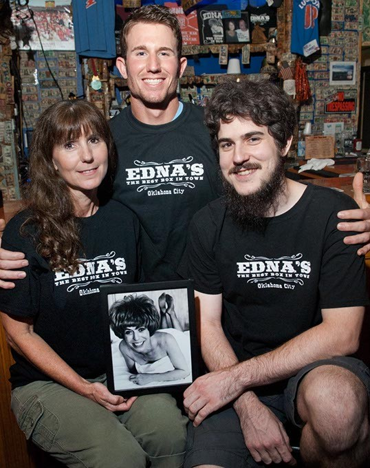 Edna's daughter, Tammy Lucas with sons, from left, Nathan Lucas and Michael Whitley, pose with a well known portrait of Edna, at the bar inside Edna's.  mh