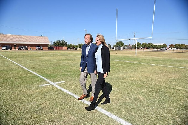 Tim and Liz McLaughlin helped start the Fields and Futures Foundation, shown walking a new football field constructed at Webster Middle School, 10-14-15. - MARK HANCOCK