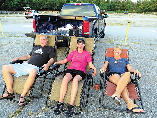 Lloyd and Charlotte Kutch (left and middle) and Brenda Bischoff join other early arrivers as they prepare for the first of two first-run movies. Lloyd wired in jacks to the back of his truck to plug in speakers especially for their visits to the Winchester. - BRETT DICKERSON
