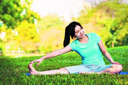Young woman doing yoga exercise on green grass - BIGSTOCK