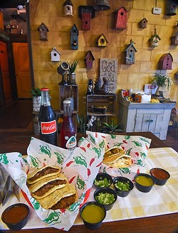 An assortment of pork crackling, chicken with cream, and beef barbacoa gorditas, with sauces and beverages if front of a homey, bird house and crafts wall at Gorditas Mexican Kitchen, 11-2-15. - MARK HANCOCK