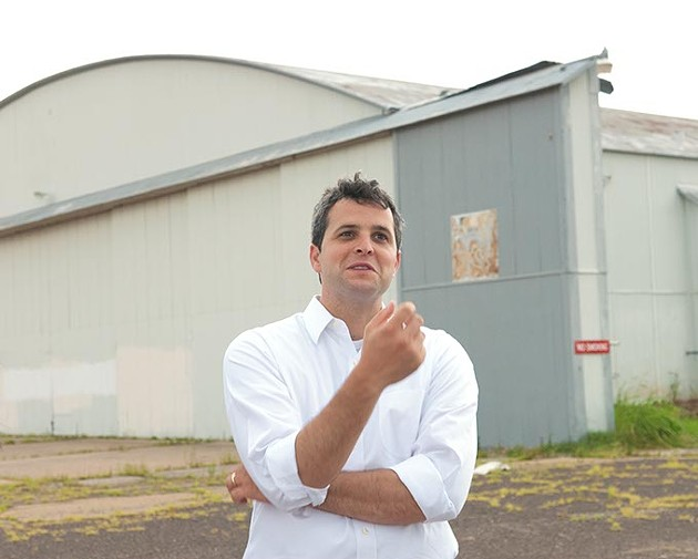 Blair Humphreys in front of a large existing hangar at the site of the Wheeler District Downtown Airpark development concept.  mh