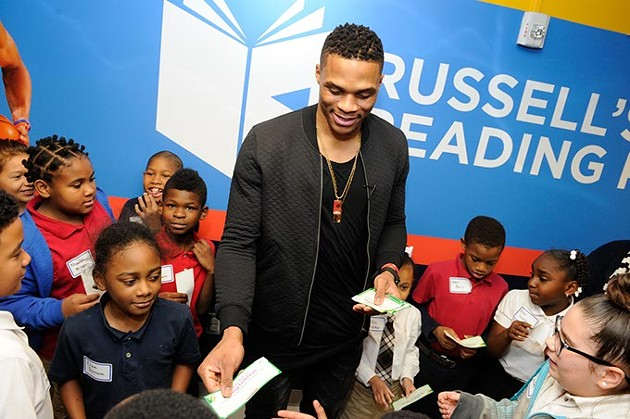 Russell Westbrook presents reading certificates to students during a book fair and opening of Russell's Reading Room at Edwards Elementary School in Oklahoma City, Tuesday, Jan. 5, 2016. - GARETT FISBECK