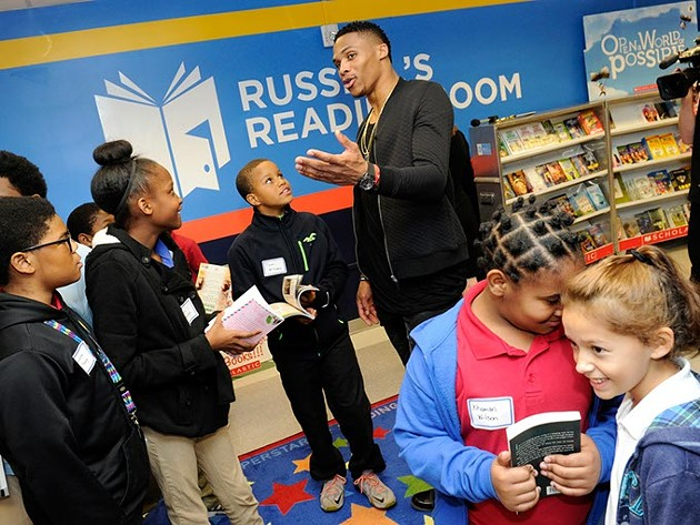 Russell Westbrook helps students pick out books during a book fair and opening of Russell's Reading Room at Edwards Elementary School in Oklahoma City, Tuesday, Jan. 5, 2016. - GARETT FISBECK