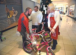 From left, Moore Oklahoma business owners, Greg Derr, and Michael Milligan bought gifts for ten children, including bicycles, and turned them over to Salvation Army volunteers, June McCoy and Terri Holcomb, at the Angel Tree in Penn Square Mall, 12-8-15. - MARK HANCOCK