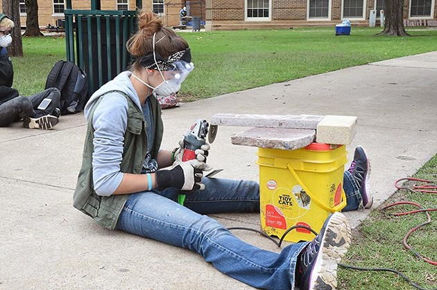 Art student Alice Dunaway forms granite pieces with an angle grinder as part of the Coming Together Park sculpture being installed on the USAO campus.  mh
