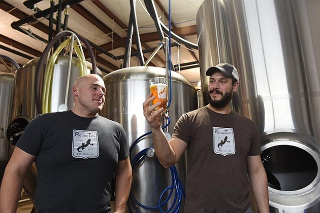Left, Kevin Hall, director of LOCAL, and Tony Tielli, with Rough Tail Brewing Company, check out one of their draw beers in the light streaming between brewing vessels in their Midwest City production facility.  mh