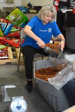 Mindy Duke seperates dog food into smaller bags at the Pet Food Pantry in Oklahoma City, Okla. - LAUREN HAMILTON