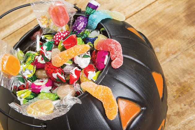 Black plastic pumpkin filled with candy wooden table - BIGSTOCK