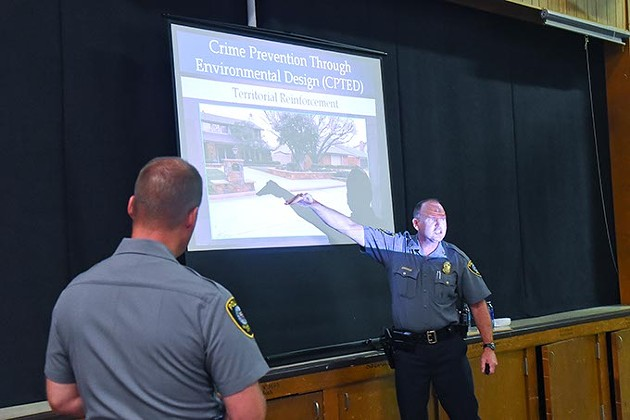 Master Sargent Robert Skalla discusses an image of a residence during his Crime preventon Through Environmental Design presentation, with Master Sergeant Robert Henderson  watching, Thursday night in south OKC.  mh