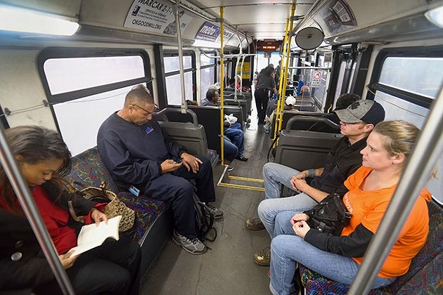 Passengers get comfortable near the rear of the Route 5 bus as it continues to board at the Embark downtown transite station, 3:30 pm, 11-20-15. - MARK HANCOCK