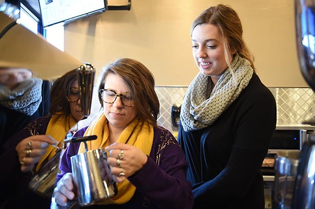 From left, Alissa Williams steams milk in a coffee drink preparation while shop owner Ally Moore watches, at Compass Coffee Shop in Edmond.  mh