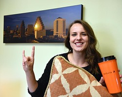 "Next to a picture of the Austin skyline while holding a burnt orange pillow and coffee container, Mary Ellen Knewtson gives the ""Hook-em-horns"" sign, at her office with The Gooden Group in Edmond, 9-29-15. - MARK HANCOCK"